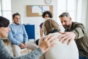 group supporting woman as she shares during Addiction Treatment Therapies in oh