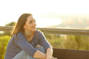 woman sitting on bridge learning about midwest detox center